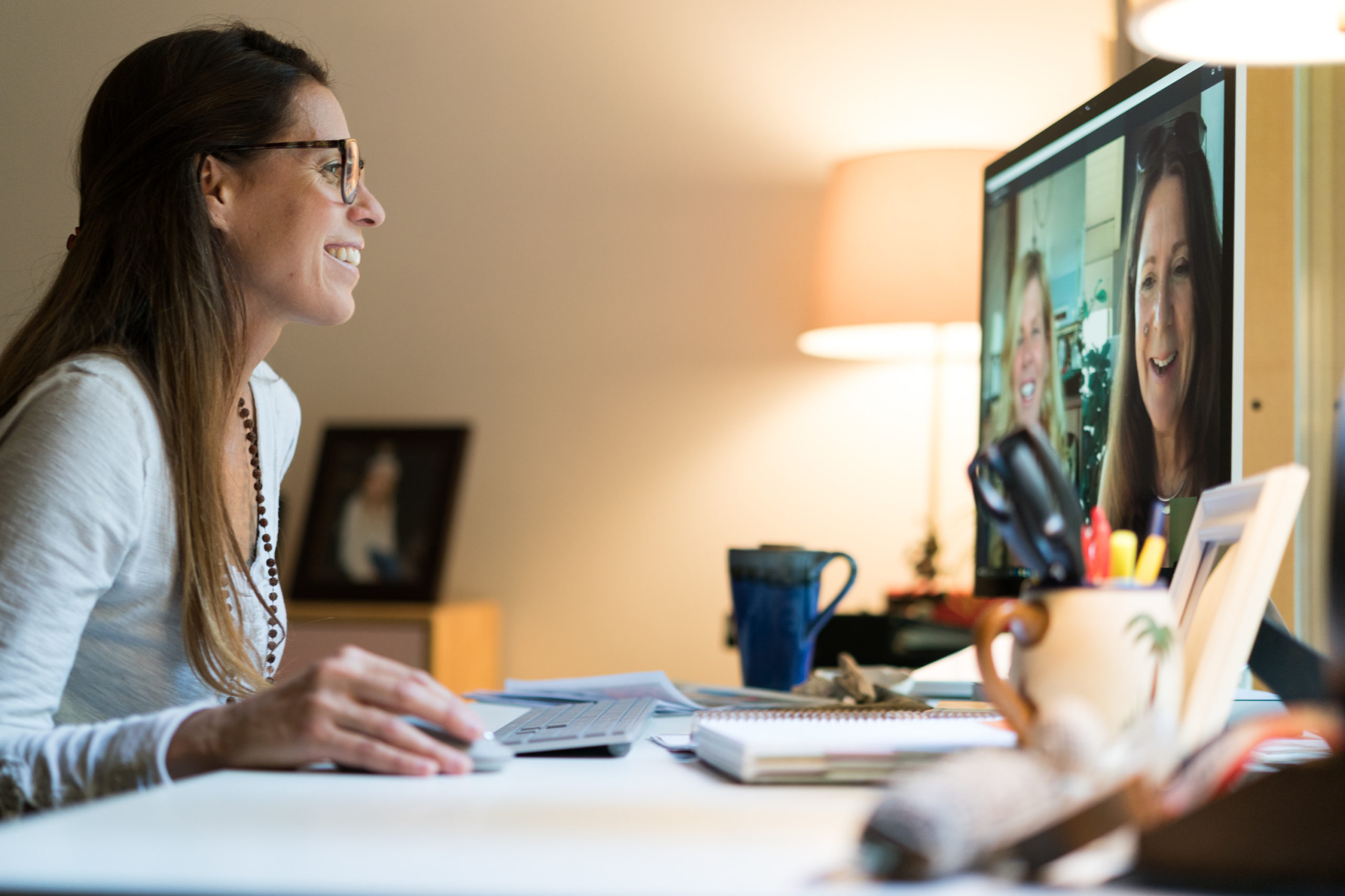 Smiling woman meeting remotely with two team members on a computer screen