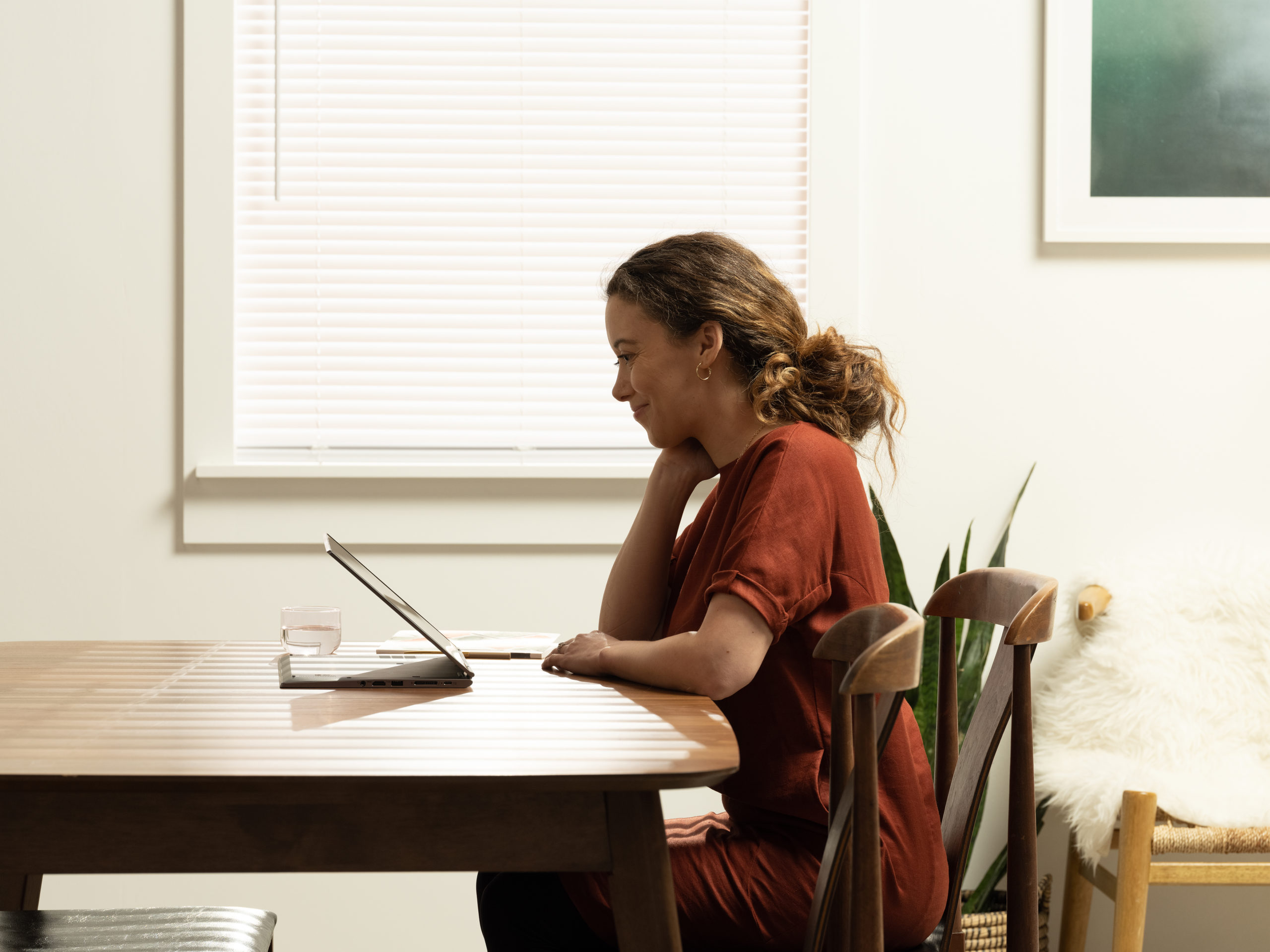 Side view of woman working on dining room table with laptop